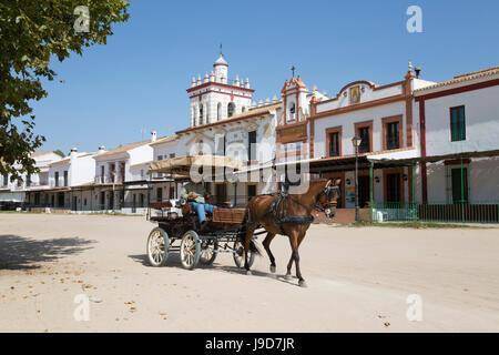 Cavallo e Carrozza a cavallo lungo le strade di sabbia con case di fraternità dietro, El Rocio, provincia di Huelva, Andalusia, Spagna, Europa