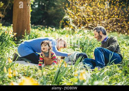 La famiglia felice seduti in giardino Foto Stock