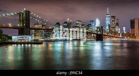 Vista panoramica del Ponte di Brooklyn con il quartiere finanziario di grattacieli al crepuscolo e nuvole di luce. La parte inferiore di Manhattan, New York City
