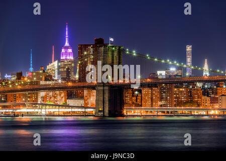 Vista notturna del Ponte di Brooklyn e grattacieli di Manhattan con l' Empire State Building illuminato in rosa. La città di New York Foto Stock
