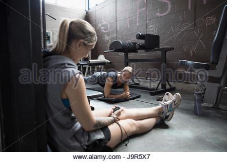Personal trainer di distribuzione client femmina facendo plank esercizio in palestra grintoso Foto Stock