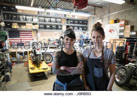 Ritratto fiducioso e sorridente motociclo femmina meccanica nel negozio di riparazioni auto Foto Stock