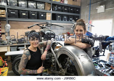 Ritratto sorridente, fiducioso femmina meccanica di motocicletta Motocicletta di fissaggio nel negozio di riparazioni Foto Stock