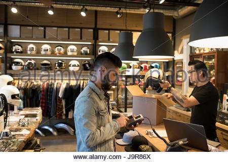 Il cliente utilizzando un lettore di carte di credito a contatore in motocicletta shop Foto Stock
