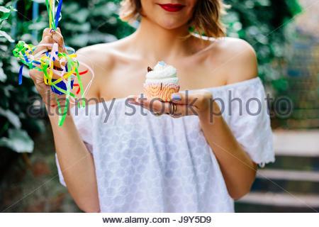 La donna è felice con la sua torta di compleanno Foto Stock