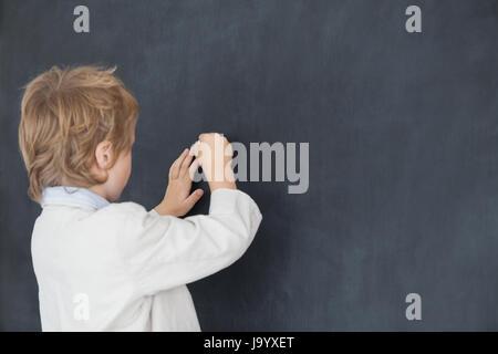 Vista posteriore del giovane ragazzo vestito come insegnante e scrive sulla lavagna nera Foto Stock