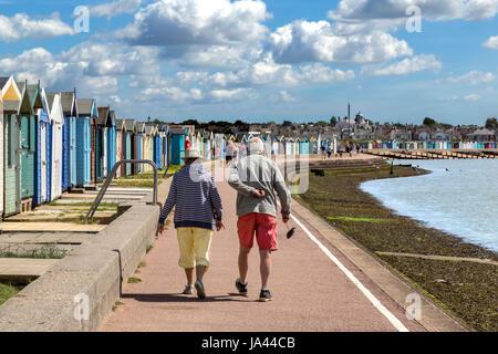 Una coppia di anziani a piedi lungo il lungomare di BRIGHTLINGSEA in Essex. L'uomo sembra soffrire di un Male all'indietro. Foto Stock