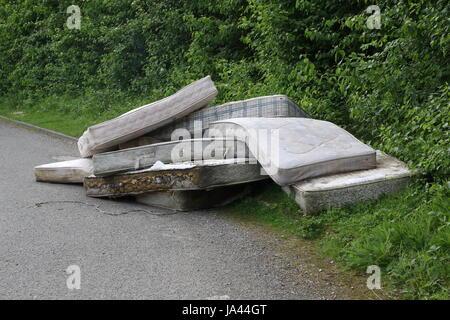 Un carico di materassi oggetto di dumping dal lato di una strada di campagna del Sussex Foto Stock