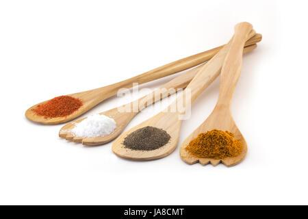 Quattro royal spezie su cucchiai di legno, sale, pepe nero, peperoncino e zafferano isolati su sfondo bianco Foto Stock