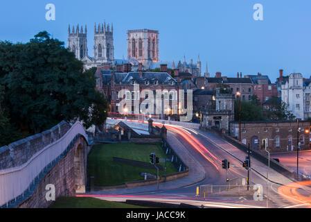 Le mura della città, strada sopra il ponte Lendal & 3 torri iconica del Minster set contro il buio del cielo della sera, incandescenza delle lampade stradali e sentieri di luce - York, GB, UK.