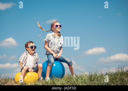 Fratello e Sorella di giocare sul campo in tempo di giorno. Bambini divertirsi all'esterno. Essi saltando su palloni Foto Stock