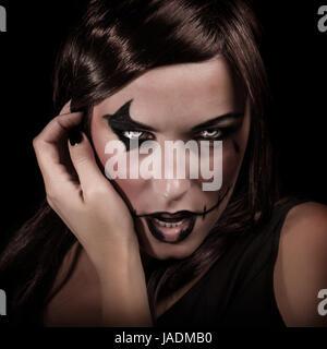 Scary Ritratto di giovane donna con il trucco aggressivo isolati su sfondo nero, terrificante strega, spooky vampiro, Foto Stock
