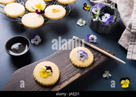 Il procedimento di preparazione di biscotti frollini con fiori commestibili sul vecchio sfondo di legno. Cibo per Foto Stock