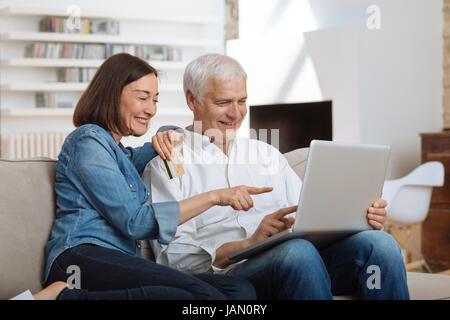 Coppia Matura collegato con il computer portatile e lo shopping online Foto Stock