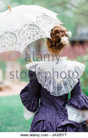 Vista posteriore di una donna vittoriana tenendo un ombrellone Foto Stock