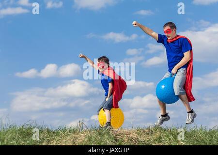 Padre e figlio del supereroe di riproduzione al giorno. Le persone aventi il divertimento all'aperto.Essi saltando Foto Stock