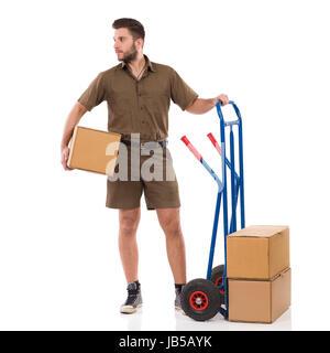 Corriere maschio è in piedi vicino a spingere il carrello, pacchetto di contenimento sotto il suo braccio e guardando Foto Stock
