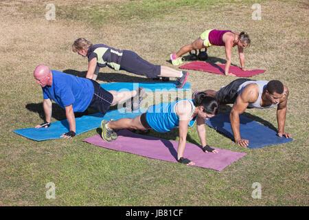 Un gruppo di cinque persone che esercitano in outdoor boot camp Foto Stock