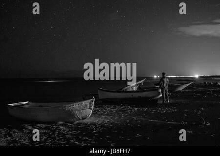 L uomo al centro delle barche guarda il cielo stellato Foto Stock