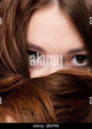 Close-up ritratto di una donna bellissima copre la faccia da lunghi peli di colore marrone