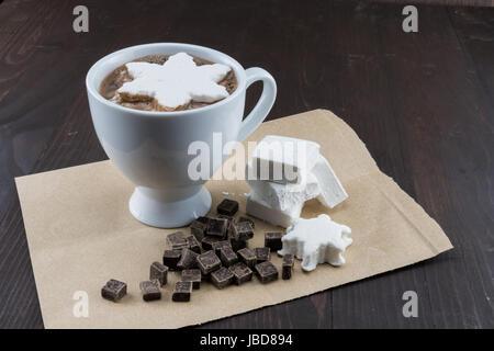 Tazza di cioccolata calda con fatti in casa Marshmallows e scaglie di cioccolato su carta marrone Foto Stock