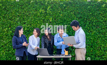 Imprenditrice e imprenditore riunione fuori ufficio con computer portatile cellulare e dispositivo tablet a foglia Foto Stock