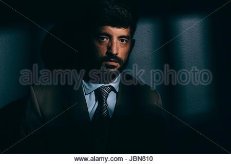 Imprenditore o prigioniero politico in cella oscura. Concetto di White Collar Crime Foto Stock