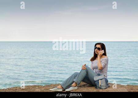 Giovane donna in jeans, in cima a strisce e scarpe da ginnastica sulla spiaggia in riva al mare. Messa a fuoco selettiva.