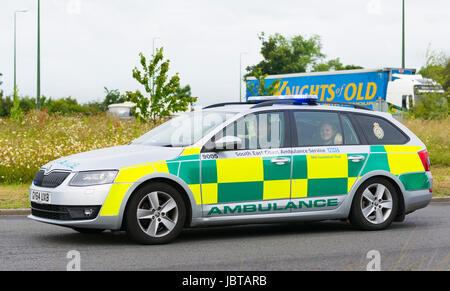 Costa sud orientale ambulanza accelerando su una rotatoria con luci blu nel Regno Unito.