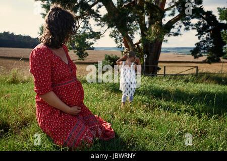 Donna incinta seduta nel campo guardando la figlia dei bimbi Foto Stock