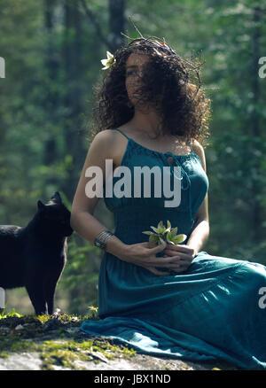 Giovane e bella donna che indossa un abito verde e una ghirlanda fatta di rami di alberi nei suoi lunghi capelli Foto Stock