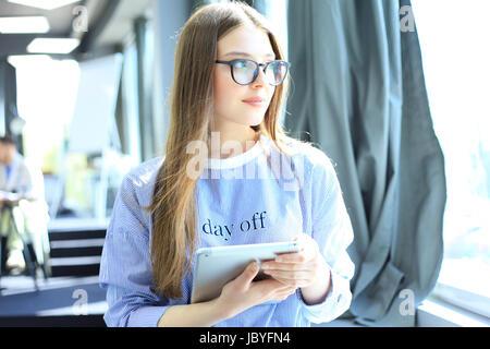 Attraente imprenditrice lavorando su una tavoletta digitale in ufficio Foto Stock