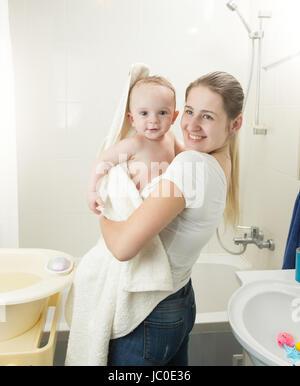 Ritratto di Madre sorridente che copre il bambino in asciugamano dopo aver vasca da bagno Foto Stock