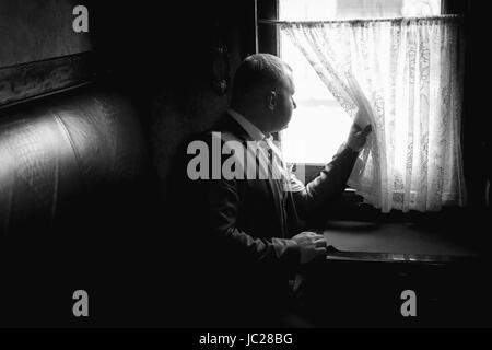 Ritratto monocromatico di elegante uomo seduto in treno coupé e guardando fuori della finestra Foto Stock