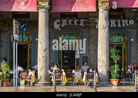 Cagliari Via Roma, le persone a rilassarsi presso le tabelle in una terrazza porticata al di fuori del Caffe Torino nel quartiere Marina di Cagliari,