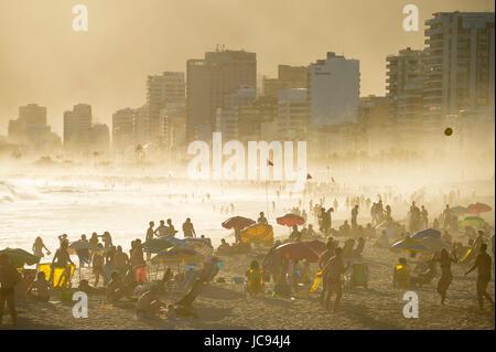 RIO DE JANEIRO - MARZO 20, 2017: sagome di persone gustano il golden misty tramonto rive della spiaggia di Ipanema a Rio de Janeiro in Brasile Foto Stock