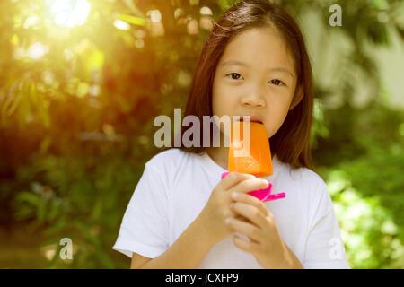 Felice ragazzo asiatico mangiare ghiaccioli gelati durante le calde giornate estive. Foto Stock