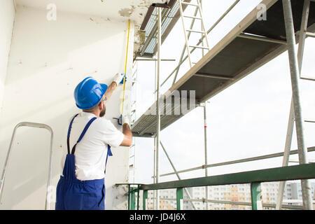 La misurazione della distanza. Lavori sul sito, il lavoratore ad alta altitudine su impalcature il lavoratore edile Foto Stock