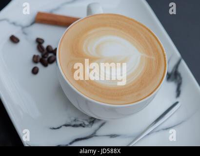 Latte art caffè. Forma di cuore ultimo arte in tazza bianca Foto Stock