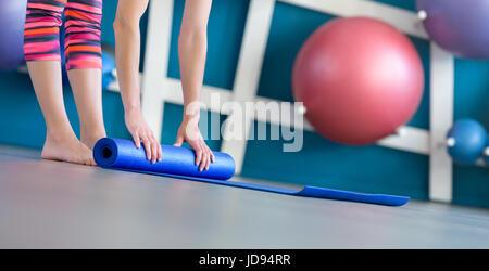 Giovane donna blu pieghevole yoga o tappetino fitness dopo il lavoro fuori. vita sana, mantenendo il concetto fit