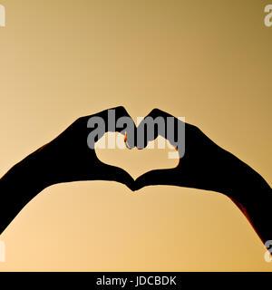 Silhouette a mano a forma di cuore Foto Stock