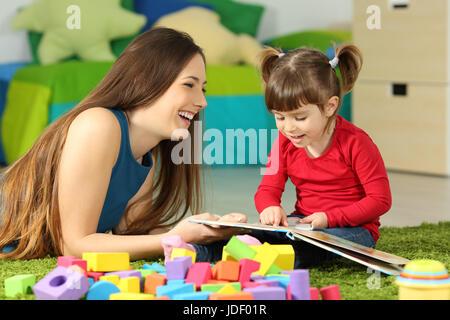 La madre e il bambino a giocare insieme con un libro sdraiato sul pavimento in camera da letto a casa con un sfondo Foto Stock