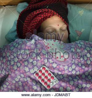Una donna europea stabilisce sotto i coperchi in letto mentre ammalati con il freddo. Foto Stock