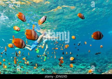 La famiglia felice - giovane in maschere per lo snorkeling immersioni subacquee profondo con pesci tropicali in Foto Stock