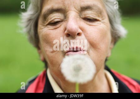 Donna anziana soffiando tarassaco in posizione di parcheggio Foto Stock