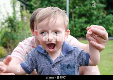 Un anno di età baby boy prendendo i primi passi Foto Stock