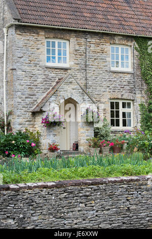 Cottage in pietra e floreali cestelli appesi e giardino frontale a Coln St Aldwyns. Cotswolds, Gloucestershire, Inghilterra Foto Stock