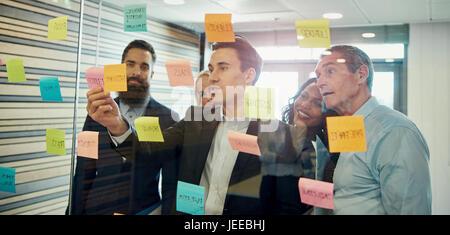 Gruppo di imprenditori il brainstorming, mettendo una nota adesiva sul vetro Foto Stock