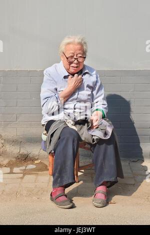 PECHINO-22 OTTOBRE 2007. Granny sedersi di fronte alla sua casa. La popolazione anziana cinese (60 anni o più) è attualmente di circa 128 milioni. Foto Stock