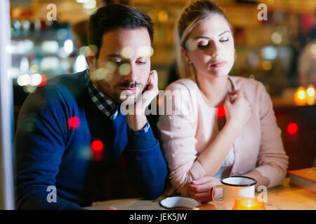 Triste giovane avente i conflitti e i problemi di relazione di udienza in bar Foto Stock